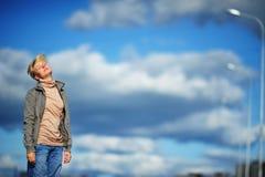 Portret droevige en beklemtoonde jonge vrouw die migraine aan hoofdpijn, blauwe hemel en wolken lijden als achtergrond Stock Afbeeldingen
