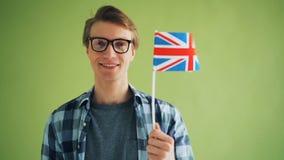 Portret dumna englishman mienia flaga ono u?miecha si? patrzeje kamer? Anglia zbiory