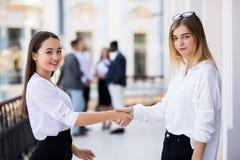 Portret dwa bizneswomanów ufny handshaking przed biznes drużyną przy spotkaniem obraz stock