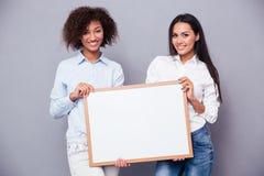 Portret dwa dziewczyny trzyma puste miejsce wsiada Obraz Royalty Free