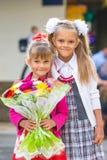 Portret dwa dziewczyny w szkolnym Wrześniu 1 - równiarka i jej młoda siostra z bukietem w rękach Zdjęcia Royalty Free