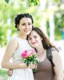 Portret dwa młodej ładnej kobiety ściska each inny w zielonym lato parku Ładna kobiety panna młoda z bukietem róże i jej Fri obraz royalty free