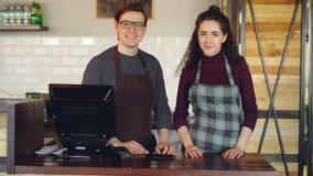 Portret dwa partnera małego biznesu właściciela stoi przy kasjera ` s biurkiem w domu i ono uśmiecha się pomyślny zbiory wideo