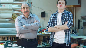 Portret dwa pracownika, stoi w warsztatowej i patrzeje kamerze poważnie Obraz Royalty Free