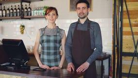 Portret dwa ufnego kelnera stoi przy kasjera ` s biurkiem w domu i ono uśmiecha się w fartuchach udany interes zbiory