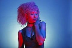 Portret dyskoteki kobieta z różowym afro włosy na błękitnym neonowym lig Fotografia Stock