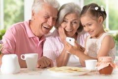 Portret dziadkowie z wnuczką używa smartphone podczas gdy pijący herbaty obrazy stock