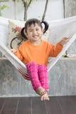 Portret dziecka toothy uśmiechnięty relaksować w odzieżowym crad i Zdjęcia Royalty Free