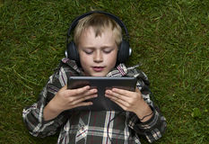 Portret dziecko blond młoda chłopiec bawić się z cyfrowym pastylka komputerem outdoors kłama na trawie Fotografia Royalty Free