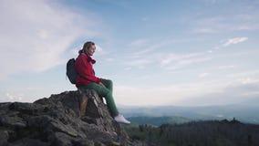 Portret dziewczyna podróżnik w górach młodej kobiety turystyczny siedzący odpoczywać na skałach przy krawędzią faleza zbiory