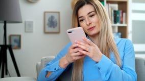 Portret dziewczyna używa urządzenie przenośne wyszukuje internet, zostaje łączący w domu cieszący się nowożytnego styl życia dosy zbiory