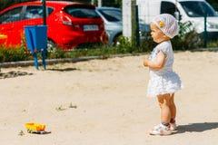 Portret dziewczyna w białej sukni troszkę białym kapeluszu z kwiatami na tle samochody i, na boisku, dziecko w zdjęcia stock