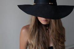 Portret dziewczyna w kapeluszu z wielkim rondem pozuje modę Zdjęcie Stock
