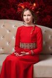 Portret dziewczyna w kwiatu wianku troszkę czerwieni smokingowym sitti i Fotografia Stock