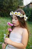 Portret dziewczyna w wianku chamomiles na ona kierownicza która wącha kwiatu, Fotografia Royalty Free