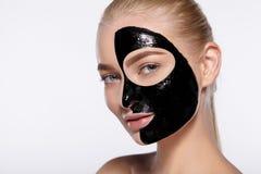 Portret dziewczyna z czarną kosmetyk maską na jej twarzy Zdjęcie Royalty Free