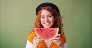 Portret dziewczyny mienia arbuza uśmiechnięta chuje twarz na zielonym tle zdjęcie wideo