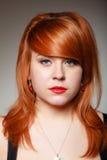 Portret dziewczyny redhaired młoda kobieta z czereśniowym benclem na szarość Zdjęcie Stock