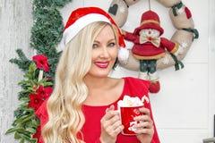 Portret Een mooi jong blondemeisje in een GLB van de Kerstman bevindt zich bij de voordeur die, met een kroon en spartakken wordt stock foto