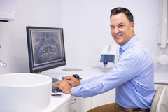 Portret egzamininuje promieniowanie rentgenowskie raport na komputerze szczęśliwy dentysta zdjęcie stock