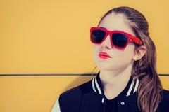 Portret elegancka dziewczyna w czerwonych okularach przeciwsłonecznych na żółtym backgro fotografia royalty free