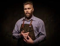 Portret elegancki fryzjer męski z brody i profesjonalisty narzędziami na ciemnym tle Zdjęcie Stock