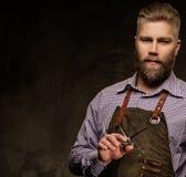 Portret elegancki fryzjer męski z brody i profesjonalisty narzędziami na ciemnym tle Zdjęcia Royalty Free