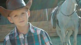 Portret elegancki mały kowboj stoi blisko purebred konia na świetle słonecznym wolno zbiory wideo