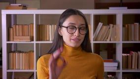 Portret eleganckiej brunetki żeński nauczyciel gestykuluje ok pokazywać sukces przy biblioteką szyldowy zbiory