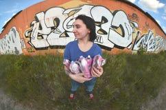 Portret emocjonalna młoda dziewczyna z czarni włosy i piercings Szeroka kąt fotografia dziewczyna z aerosolowymi farb puszkami w obrazy stock