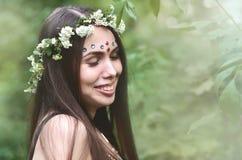 Portret emocjonalna młoda dziewczyna z kwiecistym wiankiem na jej błyszczących ornamentach na jej czole i głowie Śliczna brunetka fotografia royalty free