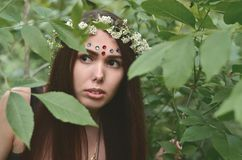 Portret emocjonalna młoda dziewczyna z kwiecistym wiankiem na jej błyszczących ornamentach na jej czole i głowie Śliczna brunetka fotografia stock
