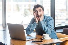 Portret emocjonalny straszący młody biznesmen w niebiescy dżinsy koszula jest siedzący w cukiernianym i krzyczeć laptope przyczyn fotografia stock