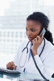 Portret żeńska lekarka używa komputer podczas gdy być na Fotografia Stock