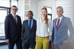 Portret etniczni ludzie biznesu stoi wpólnie w biurze fotografia stock