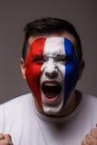 Portret Euforische schreeuw van de voetbalventilator van Frankrijk in winstspel van het nationale team van Frankrijk op grijze ac Stock Foto