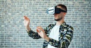 Portret facet rusza się ręki na ceglanym tle z zwiększającymi rzeczywistość szkłami zbiory wideo