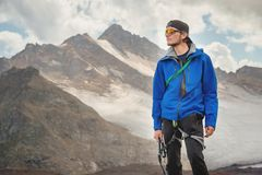 Portret fachowy przewdonik alpinista w nakrętce i okularach przeciwsłonecznych z czekanem w jego ręce przeciw obraz stock