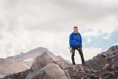 Portret fachowy przewdonik alpinista w nakrętce i okularach przeciwsłonecznych z czekanem w jego ręce przeciw fotografia royalty free