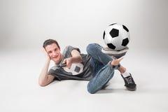 Portret fan z piłką, trzyma tv daleki na szarym tle Obrazy Stock
