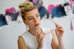 Portret fotografia młoda kobieta z szkłami i blondynami przyczepiał włosy w biel sukni szkła żelazo w jej usta między ona obraz royalty free