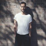 Portret gebaarde mens met tatoegering die lege witte t-shirt en zwarte jeans dragen Bakstenen muurachtergrond Verticaal model Stock Fotografie