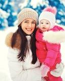 Portret gelukkig glimlachend moeder en kind in de sneeuwwinter Royalty-vrije Stock Fotografie
