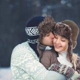 Portret gelukkig jong paar in liefde bij warme de winterdag, man zachte kussende vrouw die hoed en gebreide sweater dragen royalty-vrije stock fotografie