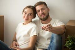 Portret gelukkig paar in nieuw huis met sleutels in handen stock fotografie