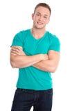 Portret: Gelukkige geïsoleerde jonge mens die groene overhemd en jeans dragen Royalty-vrije Stock Foto's