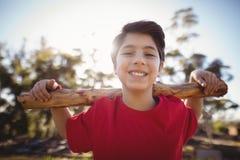Portret gelukkige jongen die met logboek tijdens hinderniscursus uitoefenen royalty-vrije stock foto's