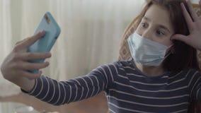 Portret gelukkige leuke tiener die een selfie dicht opnemen door haar blauwe cellphonezitting in de leunstoel thuis A stock footage