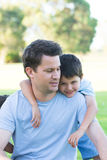 Portret gelukkige vader en zoon in park in openlucht Stock Afbeelding