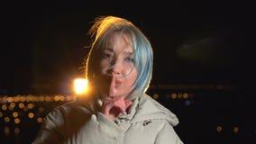 Portret Gestykuluje ciszę biała kobieta, palec na wargach, plenerowych w nocy mieście zbiory